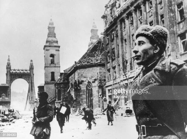 A soldier stands in the snow by the damaged Inner City Church and the Elizabeth Church in Budapest in the last few months of WW II
