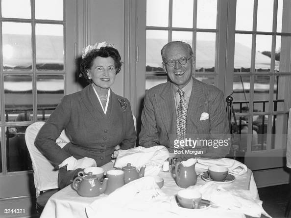 EXCLUSIVE Portrait of American financier and ambassador Joseph Kennedy and his wife Rose Kennedy sitting at table having tea in front of glass doors...