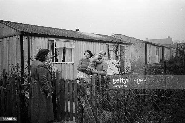 Mr and Mrs Ralph Fulcher of Chigwell Essex discuss their upcoming emigration to Canada with a neighbour over the fence of their prefab bungalow The...