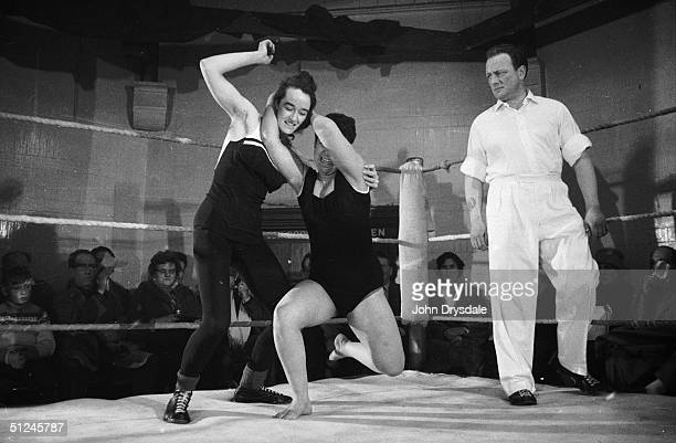 January 1964 Two women wrestlers battle it out on the mat while the referee watches on at a wrestling bout in Hawkhurst Kent