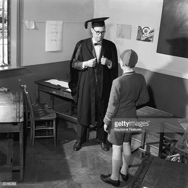 A schoolmaster in a gown and mortarboard confronts a pupil after class