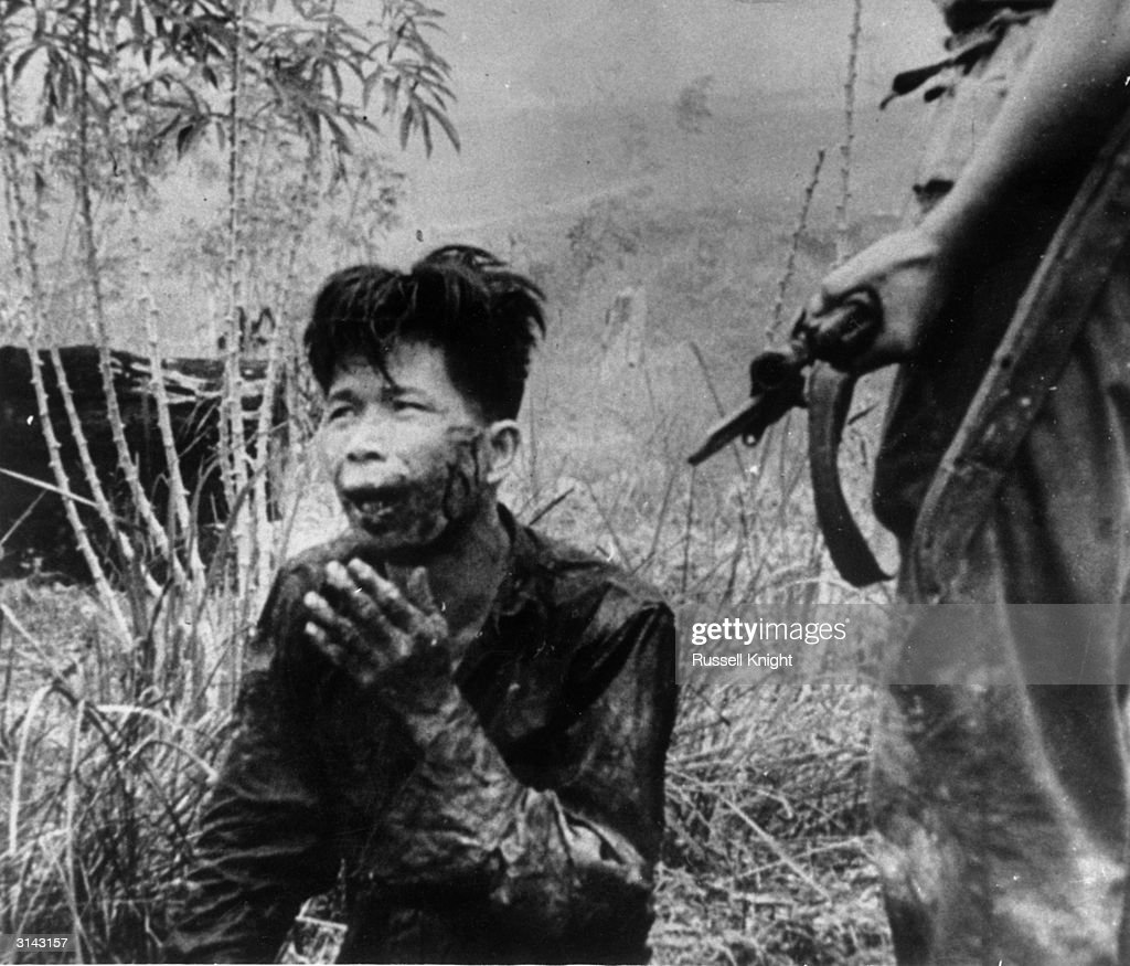 A soldier keeps close guard of a captured indonesian
