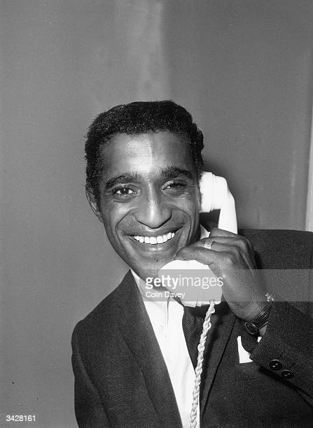 American actor singer and dancer Sammy Davis Jnr phones his wife upon his arrival at London Airport