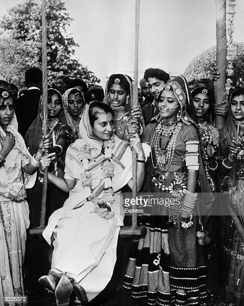 Indian premier Indira Gandhi is surrounded by women folk dancers from the province of Rajasthan while sitting on a swing erected for a Teej Festival...