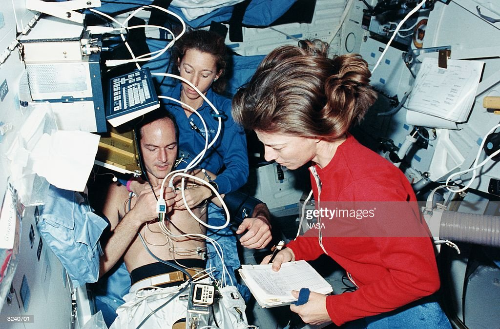 The three mission specialists on the Columbia STS-32 mission test out an Echocardiograph, a medical ultrasonic imaging system used with a lower body negative pressure unit. The test subject is G David Low, while Marsha S Ivins and Bonnie J Dunbar (right) carry out the test.
