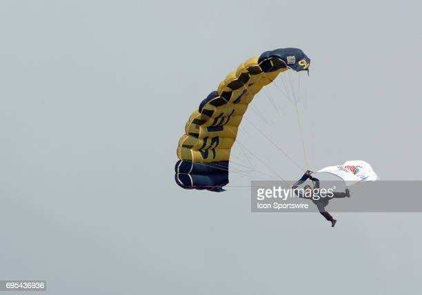 A military skydiver drops from the sky with the Rose Bowl flag during the Rose Bowl game featuring the University of Illinois Fighting Illini against...