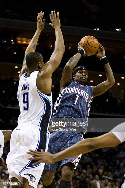 Charlotte Bobcats guard Stephen Jackson looks to pass the ball around Orlando Magic forward Rashard Lewis during an NBA basketball game at Time...