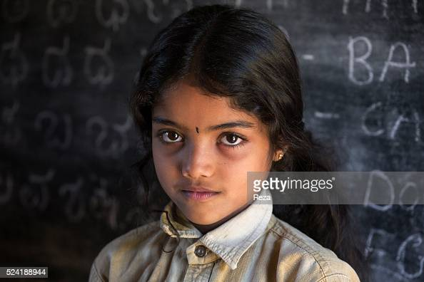 January 2013 Chickmagalur India Portrait of a little girl On the blackboard behind her the quote of the day is written 'Work when you work play when...
