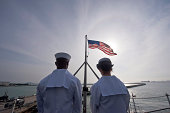 January 30, 2012 - Sailors stand by to lower the ensign as the Nimitz-class aircraft carrier USS John C. Stennis departs Singapore.