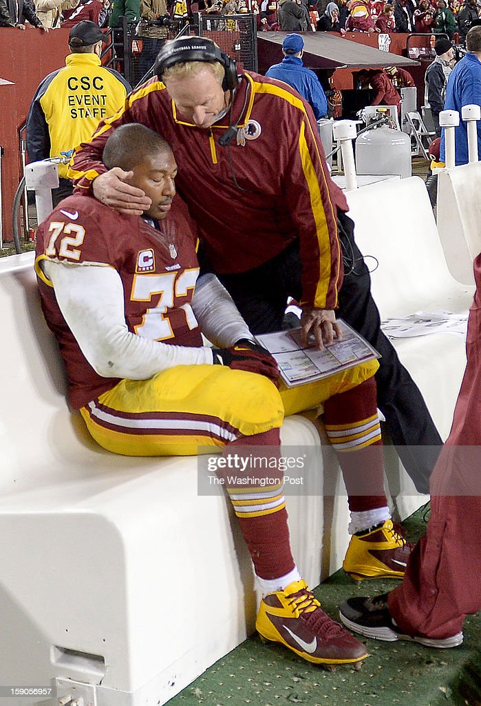 Washington Redskins defensive coordinator Jim Haslett consoles defensive end Stephen Bowen (72) as time ticks off the clock in their loss to the Seattle Seahawks at FedEx field on January 6, 2013 in Landover, MD