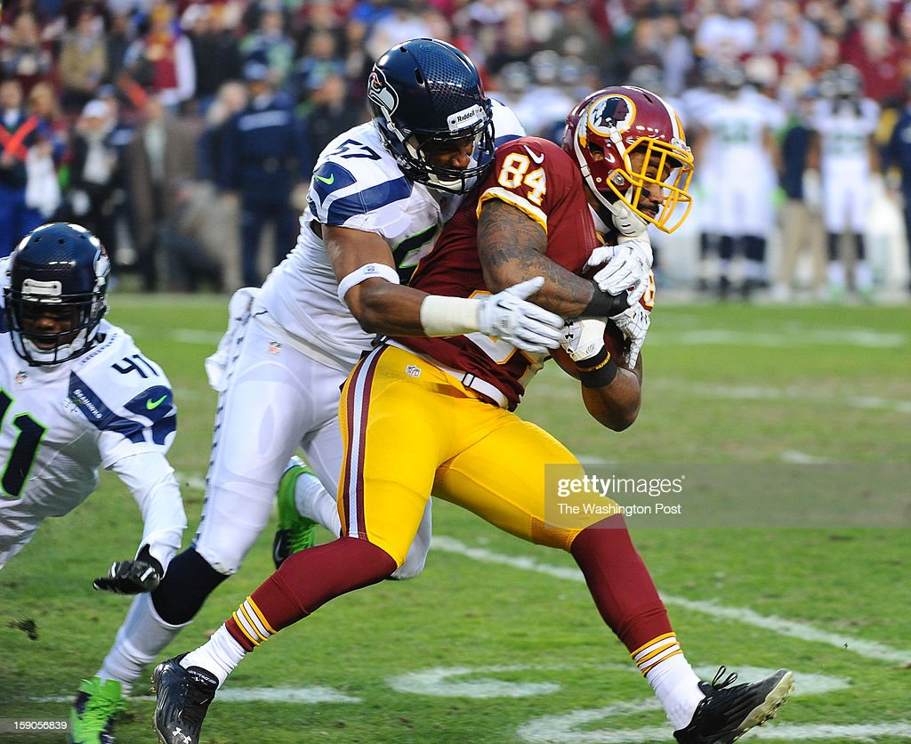 Washington Redskins tight end Niles Paul (84) is hit by Seattle Seahawks outside linebacker Mike Morgan (57) on the opening punt return at FedEx field on January 6, 2013 in Landover, MD