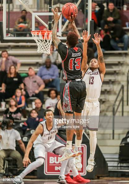 Louisiana Lafayette Ragin Cajuns guard Hayward Register shoots over the outstretched arms of Arkansas Little Rock Trojans guard Marcus Johnson Jr...