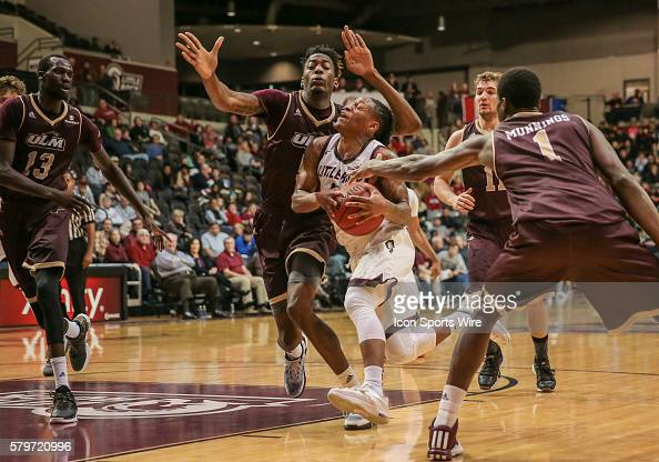 Arkansas Little Rock Trojans guard Marcus Johnson Jr drives through Louisiana Monroe Warhawks forward Travis Munnings and Louisiana Monroe Warhawks...