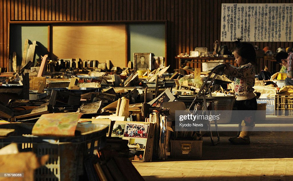 NATORI Japan A child plays among items lined up in a gymnasium in Natori Miyagi Prefecture on April 15 including family pictures school bags and toys...