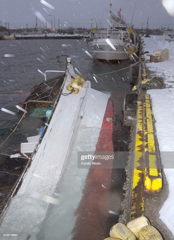 YONAGO Japan A fishing boat is submerged due to the weight of heavy snow at a port in Sakaiminato Tottori Prefecture on the Sea of Japan coast on Jan...