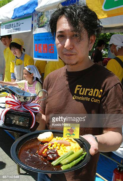 YOKOSUKA Japan A food vendor holds an omelet curry from Furano in Hokkaido northern Japan at the Yokosuka Curry Festival 2014 in Yokosuka south of...