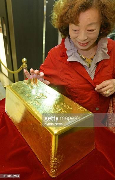 TOKYO Japan A shopper at Takashimaya department store in Tokyo's Shinjuku district touches a piece of gold bullion weighing 120 kilograms and worth...