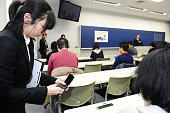 TOKYO Japan A test observer checks to see if the power is off on a test taker's cellphone at Tokyo's Taisho University on March 2 2011 A preparatory...