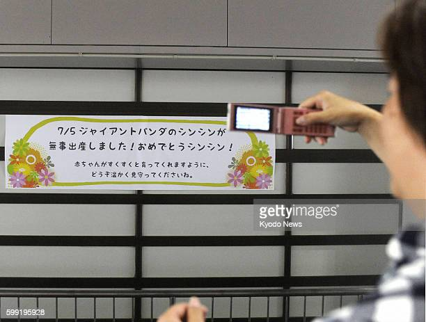 TOKYO Japan A visitor takes a picture of a sign with mobile phone at Tokyo's Ueno Zoo on July 6 2012 The sign reads 'Giant panda Shin Shin gave birth...