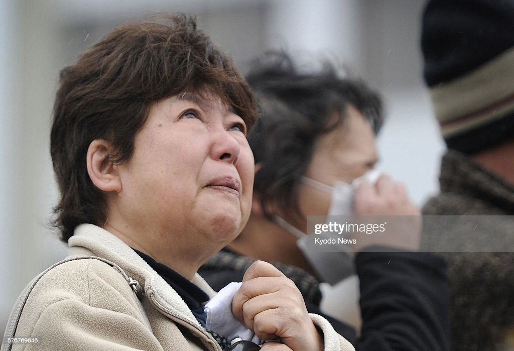 NATORI Japan A woman looks up at the sky after offering silent prayers for the victims of the massive earthquake and tsunami in Natori Miyagi...