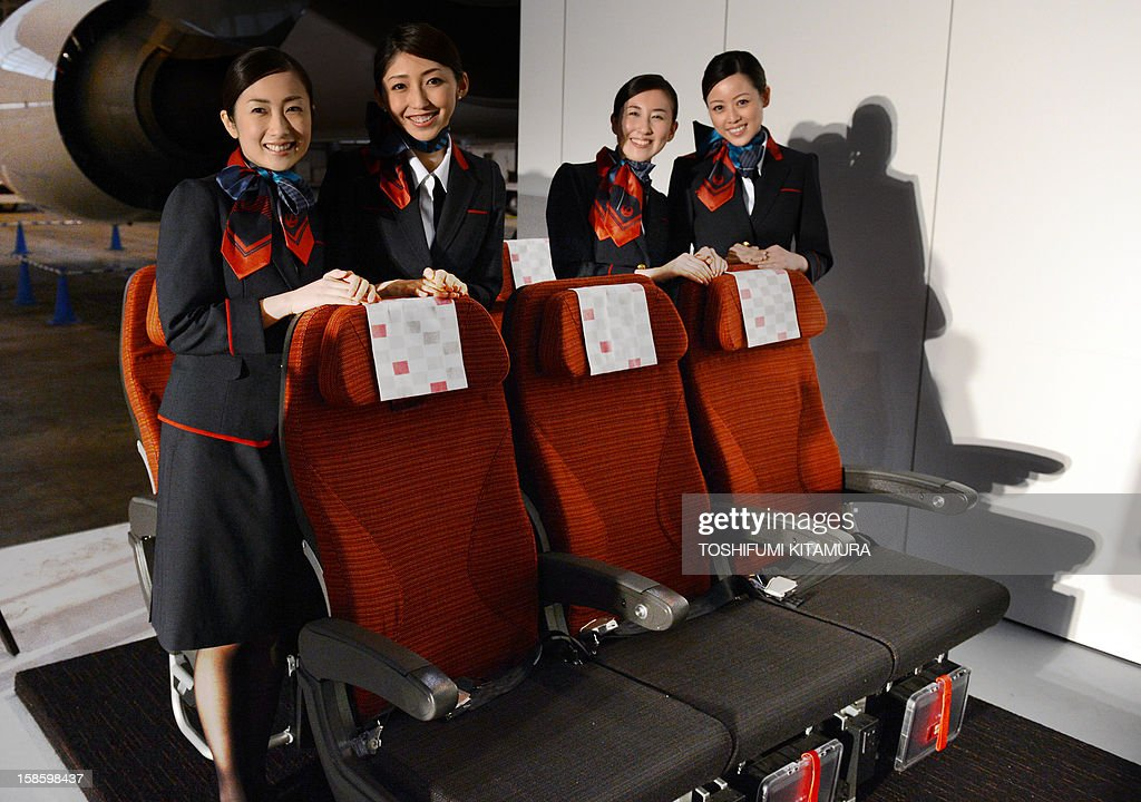 Japan Airlines cabin attendants wearing new uniforms pose behind 'JAL SKY SUIT 777,' new seats during the company's press preview in their maintenance centre at the Tokyo International airport in Tokyo on December 20, 2012. JAL displayed their new uniforms and new 'JAL SKY SUIT 777' seats for all cabin categories of their new Boeing 777-300ER jetliners during the press preview.