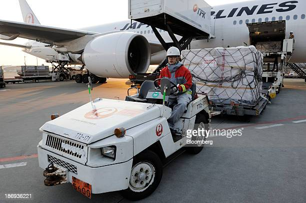 A Japan Airlines Co employee drives a cart carrying a cargo containing boxes of Beaujolais Nouveau wine at Haneda Airport in Tokyo Japan on Tuesday...