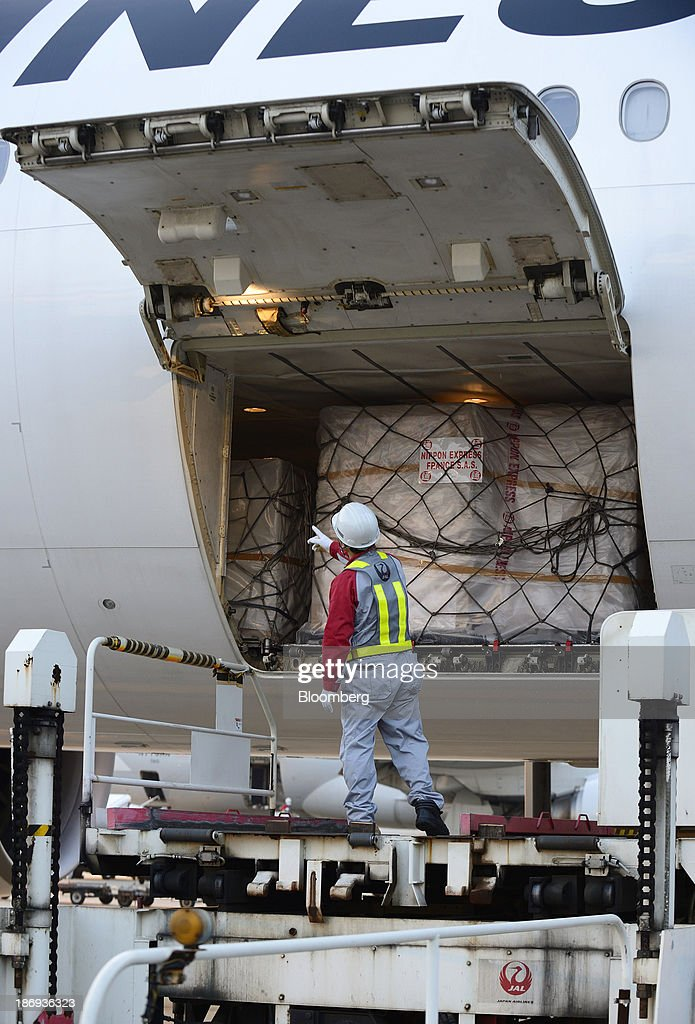 A Japan Airlines Co. (JAL) employee unload a cargo containing boxes of Beaujolais Nouveau wine from the storage space of an aircraft at Haneda Airport in Tokyo, Japan, on Tuesday, Nov. 5, 2013. Japanese appetite for Beaujolais Nouveau has made the country the largest buyer of the young wine outside France, purchasing three times the U.S., the next biggest importer. Photographer: Akio Kon/Bloomberg via Getty Images