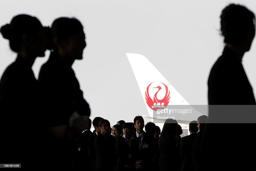 Japan Airlines Co. (JAL) group companies' new employees are silhouetted against the tail of an aircraft displaying the JAL logo during a welcoming ceremony at the company's hangar near Haneda Airport in Tokyo, Japan, on Monday, April 1, 2013. Japan's jobless rate dropped to 4.2 percent in January from 4.3 percent in December in an indication that newly elected Prime Minister Shinzo Abe's drive to boost the economy with anti-deflation policies may be paying off. Photographer: Kiyoshi Ota/Bloomberg via Getty Images