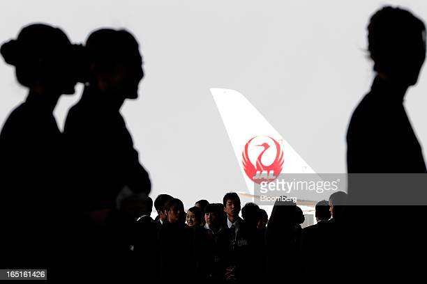 Japan Airlines Co group companies' new employees are silhouetted against the tail of an aircraft displaying the JAL logo during a welcoming ceremony...