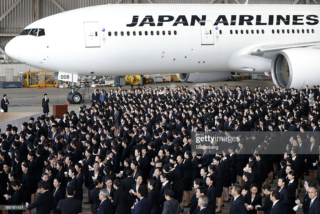 Japan Airlines Co. (JAL) group companies' new employees attend a welcoming ceremony in front of a JAL aircraft at the company's hangar near Haneda Airport in Tokyo, Japan, on Monday, April 1, 2013. Japan's jobless rate dropped to 4.2 percent in January from 4.3 percent in December in an indication that newly elected Prime Minister Shinzo Abe's drive to boost the economy with anti-deflation policies may be paying off. Photographer: Kiyoshi Ota/Bloomberg via Getty Images