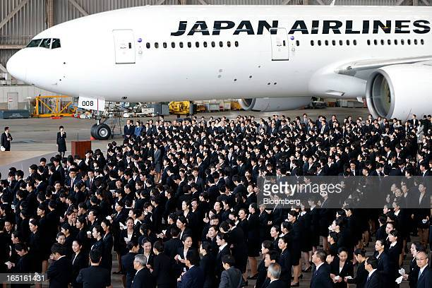 Japan Airlines Co group companies' new employees attend a welcoming ceremony in front of a JAL aircraft at the company's hangar near Haneda Airport...