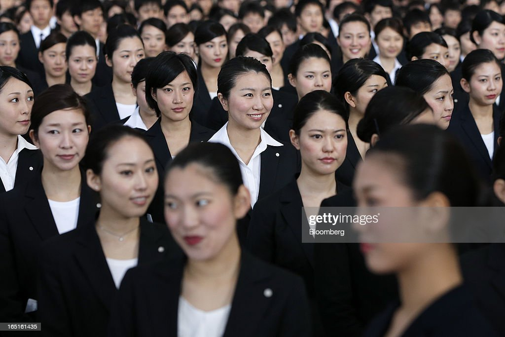 Japan Airlines Co. (JAL) group companies' new employees attend a welcoming ceremony at the company's hangar near Haneda Airport in Tokyo, Japan, on Monday, April 1, 2013. Japan's jobless rate dropped to 4.2 percent in January from 4.3 percent in December in an indication that newly elected Prime Minister Shinzo Abe's drive to boost the economy with anti-deflation policies may be paying off. Photographer: Kiyoshi Ota/Bloomberg via Getty Images