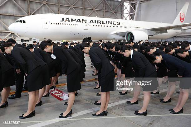 Japan Airlines Co group companies' new employees bow during a welcoming ceremony at the company's hangar near Haneda Airport in Tokyo Japan on...
