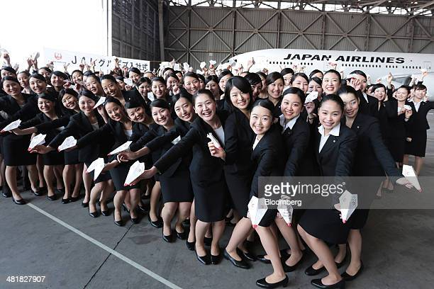 Japan Airlines Co group companies' new employees hold paper planes while posing for a photograph following a welcoming ceremony at the company's...