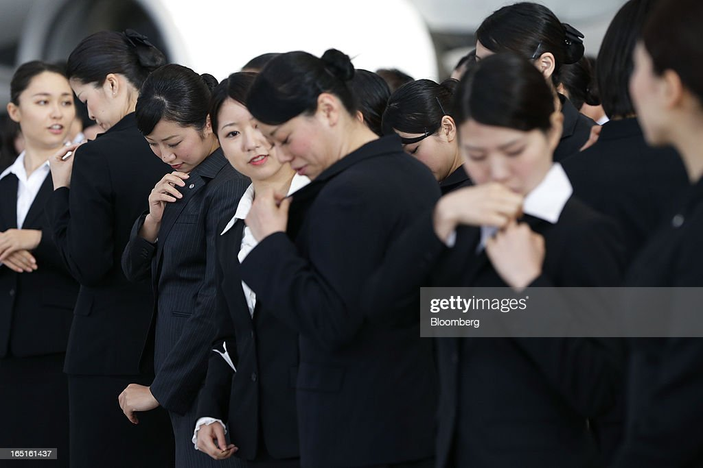 Japan Airlines Co. (JAL) group companies' new employees inspect pins on their lapels during a welcoming ceremony at the company's hangar near Haneda Airport in Tokyo, Japan, on Monday, April 1, 2013. Japan's jobless rate dropped to 4.2 percent in January from 4.3 percent in December in an indication that newly elected Prime Minister Shinzo Abe's drive to boost the economy with anti-deflation policies may be paying off. Photographer: Kiyoshi Ota/Bloomberg via Getty Images