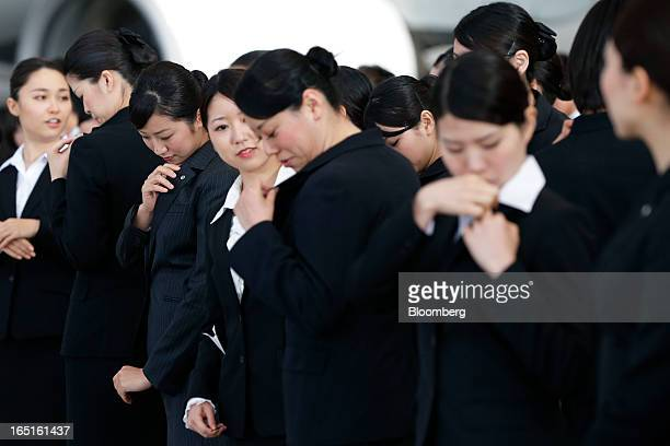 Japan Airlines Co group companies' new employees inspect pins on their lapels during a welcoming ceremony at the company's hangar near Haneda Airport...