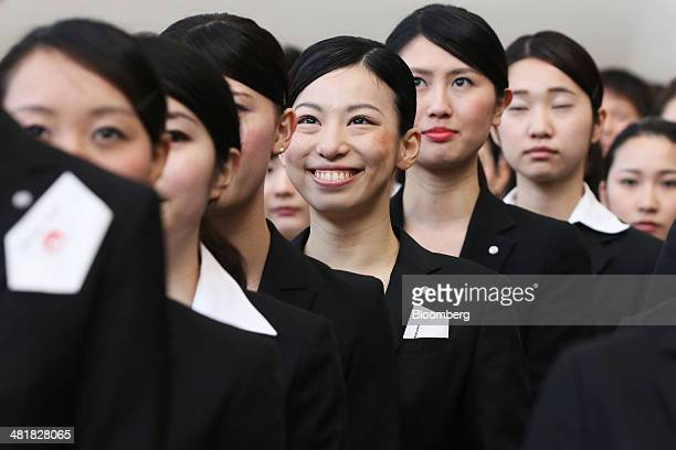 Japan Airlines Co group companies' new employees line up ahead of a welcoming ceremony at the company's hangar near Haneda Airport in Tokyo Japan on...