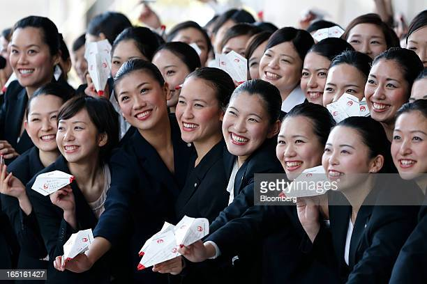 Japan Airlines Co group companies' new employees pose for photographs while holding paper planes during a welcoming ceremony at the company's hangar...