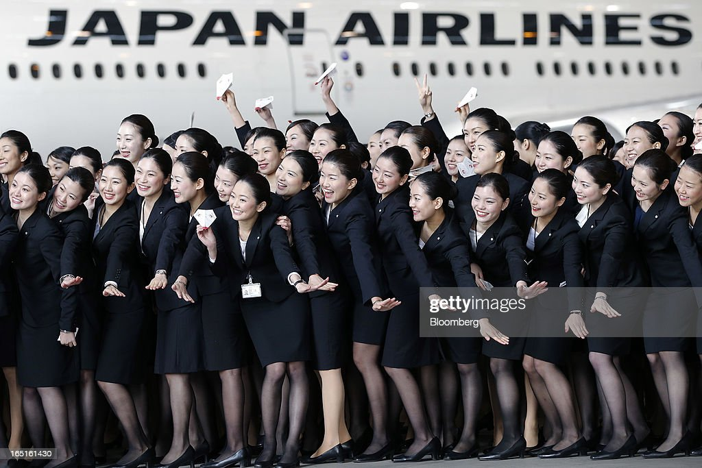 Japan Airlines Co. (JAL) group companies' new employees pose for photographs in front of a JAL aircraft during a welcoming ceremony at the company's hangar near Haneda Airport in Tokyo, Japan, on Monday, April 1, 2013. Japan's jobless rate dropped to 4.2 percent in January from 4.3 percent in December in an indication that newly elected Prime Minister Shinzo Abe's drive to boost the economy with anti-deflation policies may be paying off. Photographer: Kiyoshi Ota/Bloomberg via Getty Images