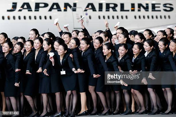 Japan Airlines Co group companies' new employees pose for photographs in front of a JAL aircraft during a welcoming ceremony at the company's hangar...