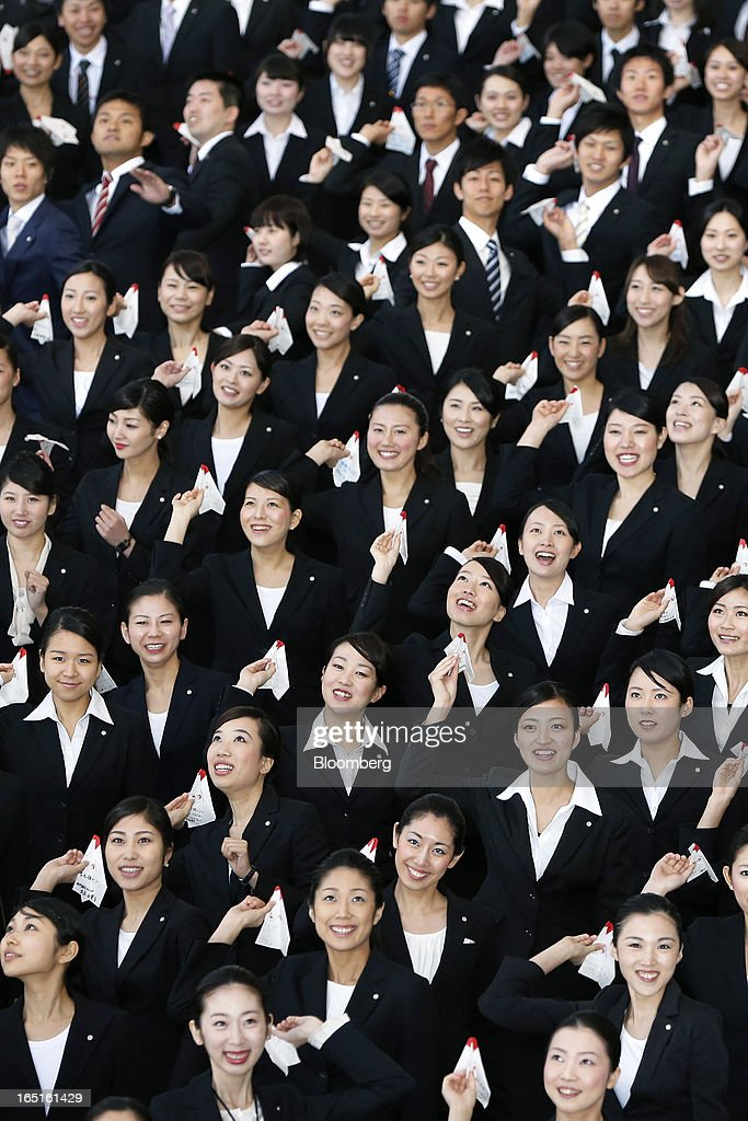 Japan Airlines Co. (JAL) group companies' new employees prepare to release paper planes during a welcoming ceremony at the company's hangar near Haneda Airport in Tokyo, Japan, on Monday, April 1, 2013. Japan's jobless rate dropped to 4.2 percent in January from 4.3 percent in December in an indication that newly elected Prime Minister Shinzo Abe's drive to boost the economy with anti-deflation policies may be paying off. Photographer: Kiyoshi Ota/Bloomberg via Getty Images