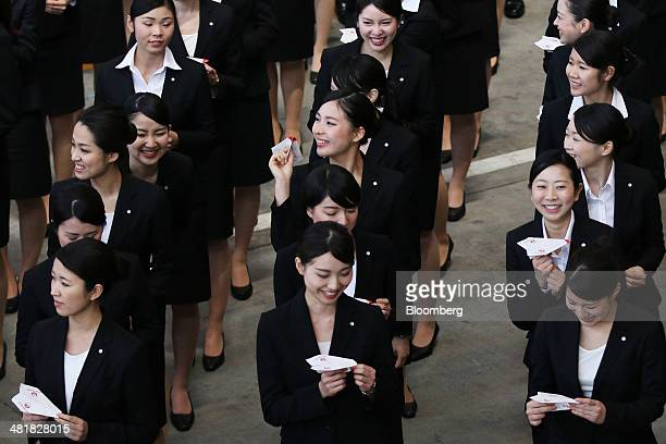 Japan Airlines Co group companies' new employees prepare to release paper planes during a welcoming ceremony at the company's hangar near Haneda...