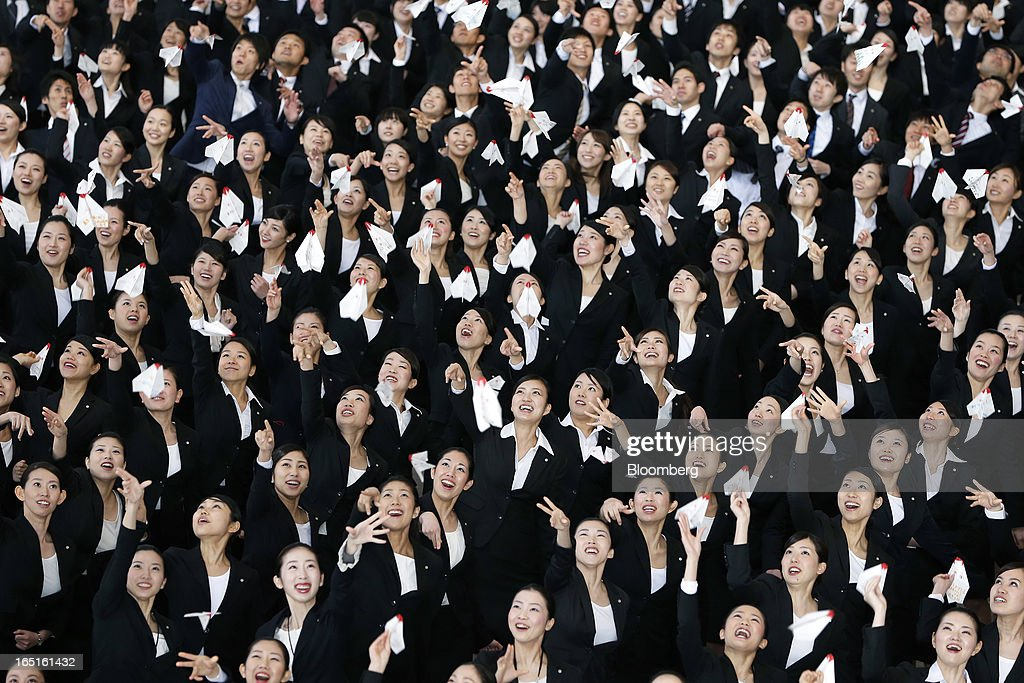 Japan Airlines Co. (JAL) group companies' new employees release paper planes during a welcoming ceremony at the company's hangar near Haneda Airport in Tokyo, Japan, on Monday, April 1, 2013. Japan's jobless rate dropped to 4.2 percent in January from 4.3 percent in December in an indication that newly elected Prime Minister Shinzo Abe's drive to boost the economy with anti-deflation policies may be paying off. Photographer: Kiyoshi Ota/Bloomberg via Getty Images