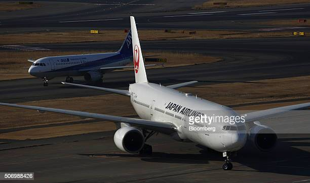 A Japan Airlines Corp right and an All Nippon Airways Co aircraft taxi at Haneda Airport in Tokyo Japan on Tuesday Jan 26 2016 JAL and ANA are...