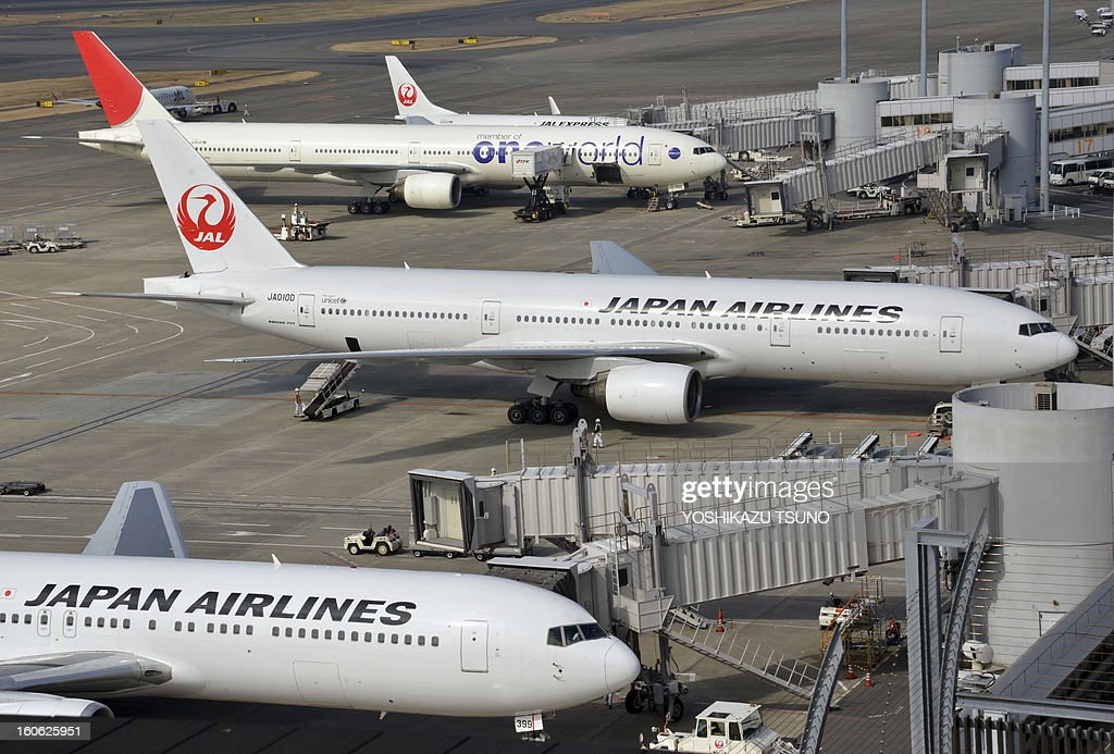Japan Airlines (JAL) jet liners, including a Boeing 777 (C) park at Tokyo's Haneda airport on February 4, 2013. JAL said that its net profit in the nine months to December slipped 3.7 percent to 1.52 billion USD, but the carrier boosted its full-year profit estimate. JAL and rival All Nippon Airways (ANA) have been hit by the worldwide grounding of Boeing's Dreamliner following an emergency landing by an ANA domestic flight earlier this month. AFP PHOTO / Yoshikazu TSUNO
