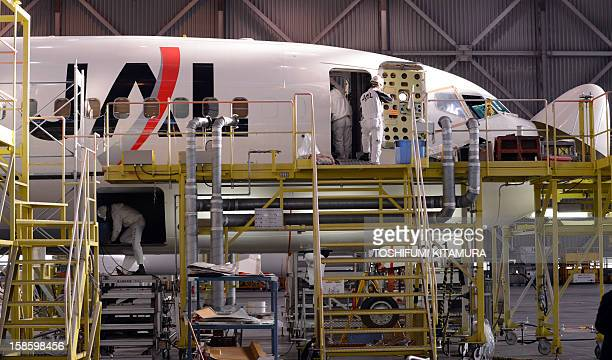 Japan Airlines mechanics maintain the company's Boeing 767 jetliner at their maintenance centre in the Tokyo International airport in Tokyo on...
