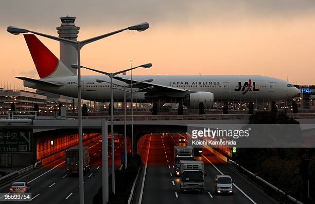 Japan Airlines passenger plane heads to the runway which is located over the highway at Tokyo International Airport on January 6 2010 in Tokyo Japan...