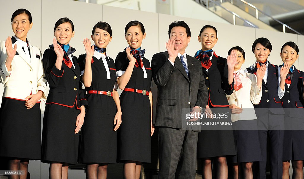 Japan Airlines president Yoshiharu Ueki (C) waves with cabin attendants (L) and ground service staff (R) in their new uniforms during the company's press preview in their maintenance centre at the Tokyo International Airport in Tokyo on December 20, 2012. JAL displayed their new uniforms and new 'JAL SKY SUIT 777' seats for all cabin categories of their new Boeing 777-300ER jetliners during the press preview.