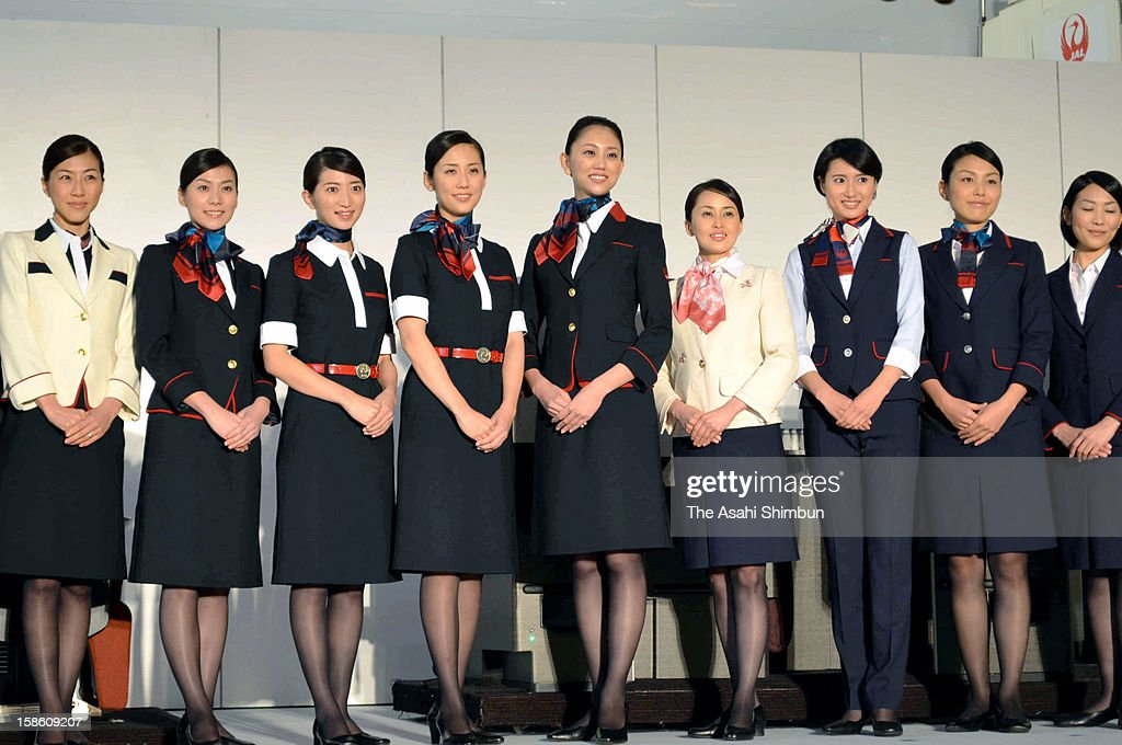 Japan Airlines staffs poses for photographs with their new uniforms, designed by Keita Maruyama, at the press preview at Tokyo International Airport on December 20, 2012 in Tokyo, Japan. The uniforms will be worn by 26,700 JAL staff members including flight crew, cabin attendants and ground staff, from the begining of fiscal year 2013.
