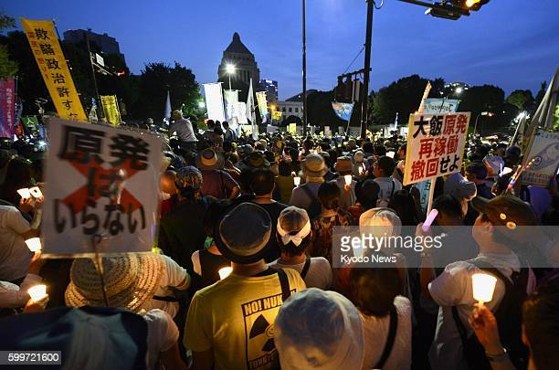 TOKYO Japan Antinuclear protesters gather holding candles in front of the Diet building in Tokyo on July 29 2012 People lit candles to surround the...